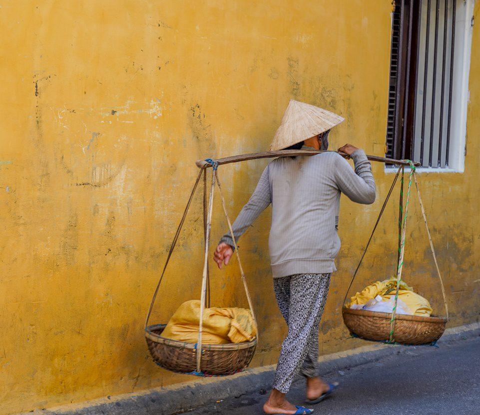 Woman carrying baskets in Hoi An Vietnam