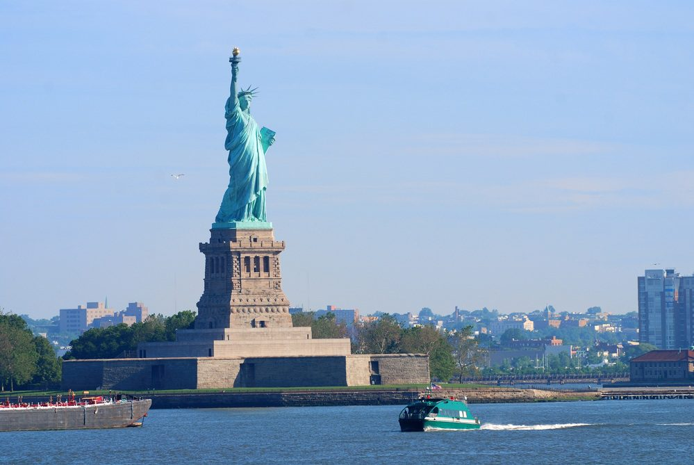 New York City Statue of Liberty with boat in Manhattan over Hudson River